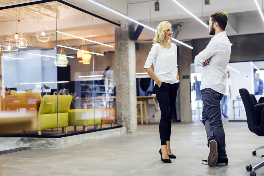 Two colleagues chatting in a modern office